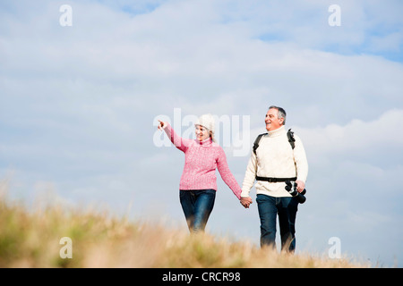 Pareja caminando de la mano en el prado Foto de stock