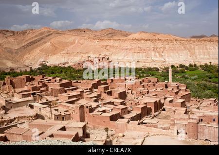 Típico pueblo de casas con paredes de barro con una mezquita y pequeños campos de un oasis fluviales, las montañas del Alto Atlas, Marruecos, África Foto de stock