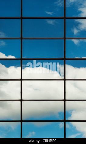 Cielo azul y las nubes reflejan en bloque de oficinas de vidrio. Londres