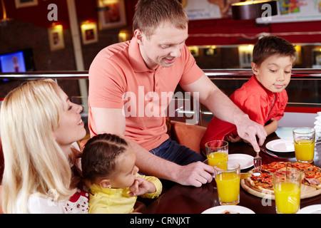 Familia reunida para disfrutar de pizzas en la pizzería local