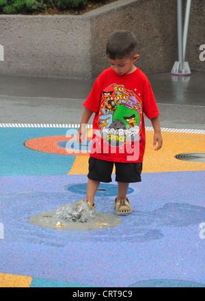 Un niño juega con un chorro de agua en un parque temático en Orlando, Florida