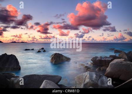 Nubes sobre la bahía de Ste Anne al atardecer visto desde el extremo norte de La Digue de las Seychelles Foto de stock
