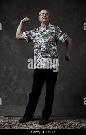 Retrato de un hombre senior flexionando los músculos