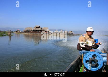 Barquero birmano conduciendo a través de pueblo flotante del lago Inle, el estado de Shan, en Myanmar, en el sudeste de Asia