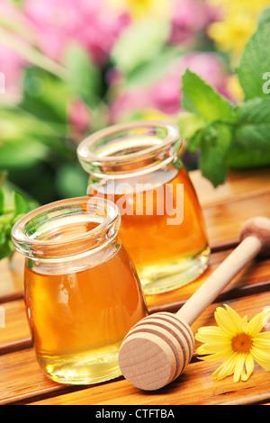 La Miel en tarros de vidrio con flores de fondo.