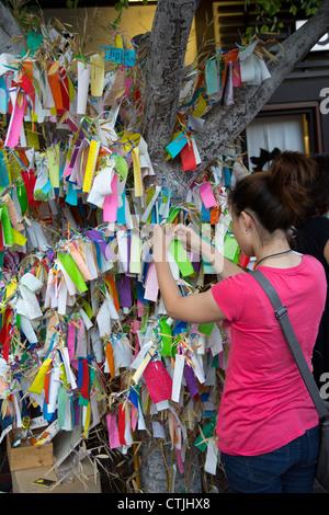 Una mujer añade su deseo de un Wishing Tree en el barrio de Little Tokyo de Los Ángeles