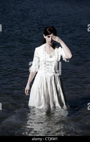 Una mujer en un vestido blanco de estilo victoriano, de pie en el agua y mantiene un ojo sobre Foto de stock