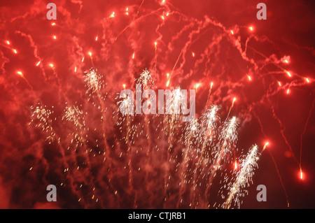 Fuegos artificiales de color rojo brillante y cohetes contra un cielo negro