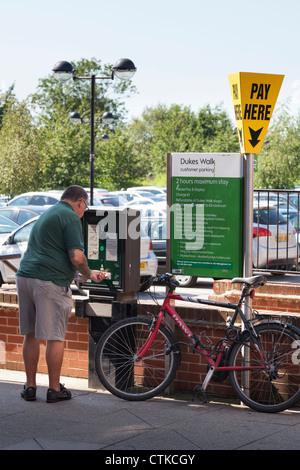 Hombre comprar ticket de aparcamiento del centro de la ciudad aparcamiento pago y mostrar la máquina