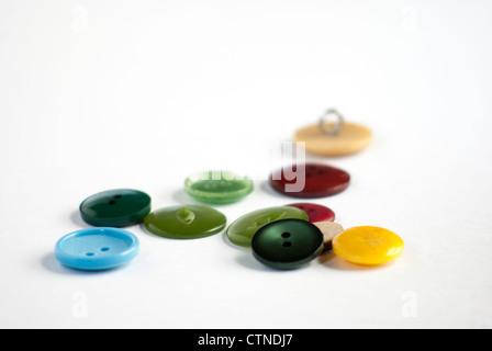 Una variedad única de coloridos botones reciclados sobre un fondo blanco.