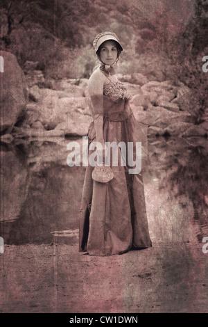 Una joven en un período vestido parado en la orilla de un lago Foto de stock