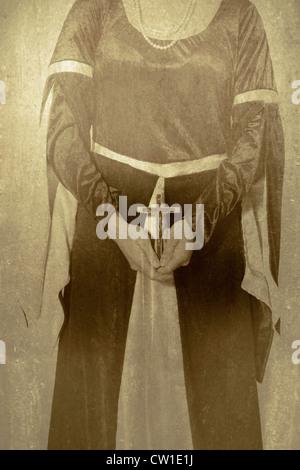 Una mujer en vestido Victoriano sosteniendo un crucifijo en sus manos Foto de stock