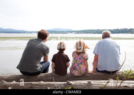 Los niños por río con padre y abuelo