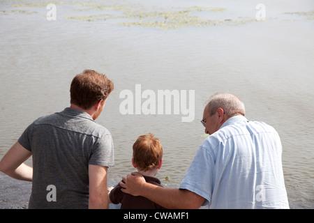 Boy en el río con padre y abuelo