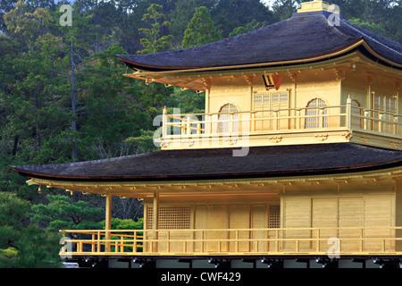 Bien vista recortada del pabellón oriental con paredes cubiertas con láminas de oro y el bosque de pinos en el fondo Foto de stock