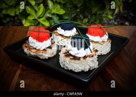 Canapés de caviar rojo y negro decorado con cebollino.