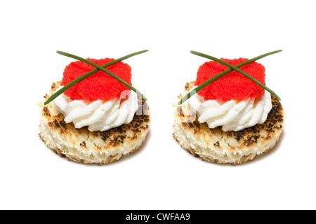 Canapés de caviar rojo y negro decorado con cebollino, sobre fondo blanco.