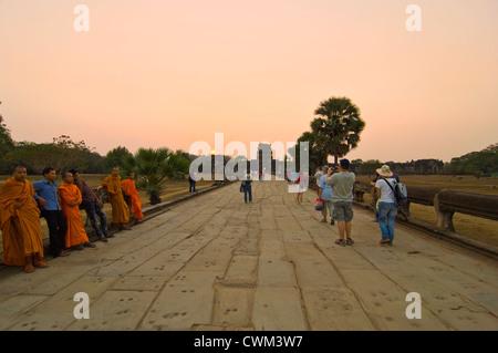 Vista horizontal de monjes sentados a lo largo de la calzada de Naga en el sol vespertino en Angkor Wat
