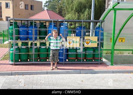 Macho joven muchacho polaco de los 6 años de edad mostrando sus músculos bíceps delante de los depósitos de gas en la estación de gasolina. Rzeczyca Polonia Central