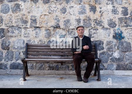 Anciano sentado en el banco de madera, Sicilia, Italia Foto de stock