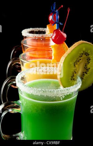 El grupo de cuatro copas de vino con coloridas bebidas cócteles, decorados con frutas y azúcar negra sobre el mostrador de bar