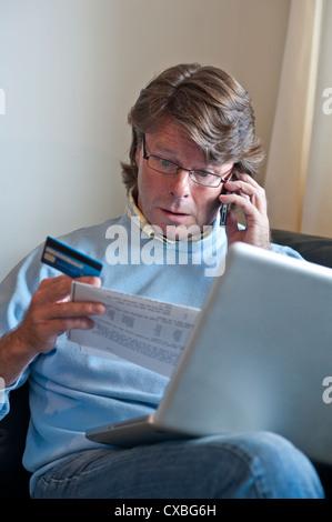 LOS ESTADOS DE CUENTA DE LA TARJETA BANCARIA preocupaban al hombre maduro en casa con un ordenador portátil en el banco de crédito por fraude de cheques de teléfono transacciones financieras con tarjeta