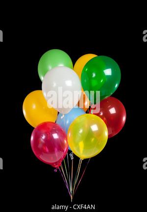 Bouquet de varios globos de colores sobre un fondo negro Foto de stock