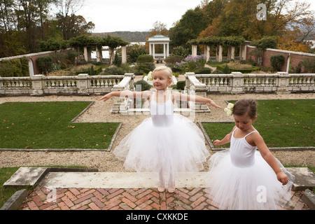 Las niñas en tutu's Dancing en un jardín. Foto de stock