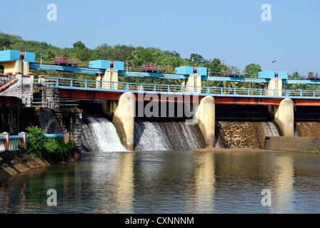 La presa de riego en Kerala, India y Escena de agua que fluye a través del vertedero de la Represa Aruvikkara persianas