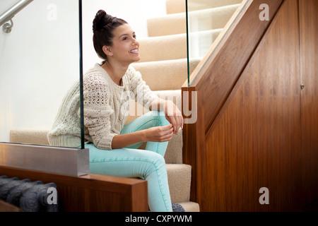 Mujer joven sentada en las escaleras, sonriendo