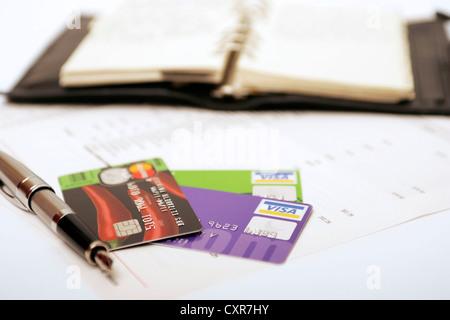 Organizador de plumas, tarjetas de débito y crédito de las deudas de la organización escrito en diario de pagos, facturas que pagar en la parte superior de la declaración