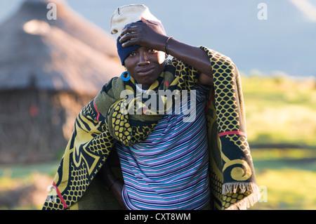 Los jóvenes basotho hombre vestido con un traje tradicional, una cabaña en la parte posterior, el Drakensberg, el Foto de stock