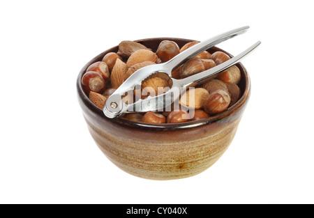Las nueces enteras en un recipiente con un cracker aislado contra un blanco