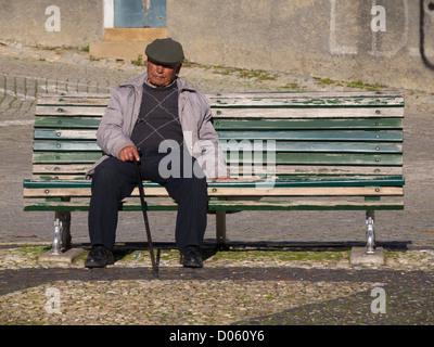 Lone anciano sentado en una banca del parque Foto de stock