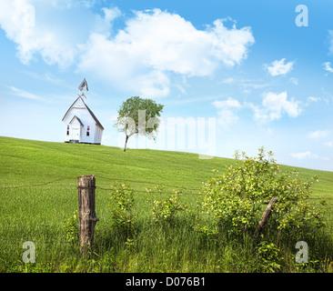 Antiguo país school house en una colina frente a un cielo azul