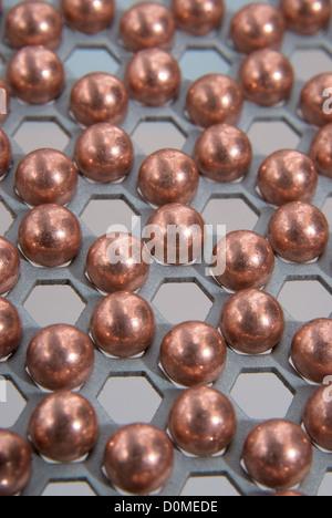 Poco bolas metálicas en el patrón de panal metálico Foto de stock