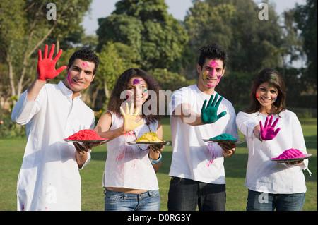 Amigos mostrando sus manos en color Holi Foto de stock