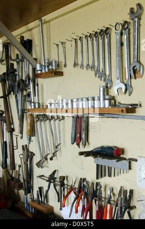 Surtido de herramientas de bricolaje colgados en un armario de madera contra una pared.