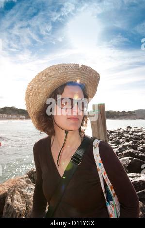 Paguera, Mallorca, España, una mujer con un sombrero de paja y gafas de sol en la playa