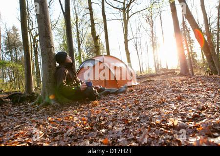 Hombre bebiendo café por carpa en el bosque