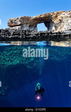 Split shot mitad y mitad con diver y arco de roca ventana azul en el Mar Mediterráneo cerca de Gozo, Malta
