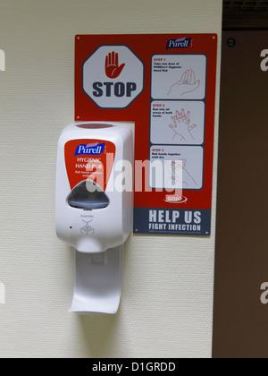 Lavar a mano gel antiséptico desinfectante dispensador montado en una pared en un hospital en el Reino Unido el norovirus
