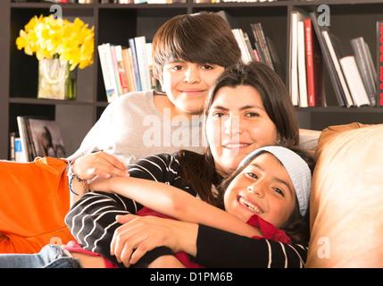Madre hispana en el sofá con hijo e hija. Foto de stock