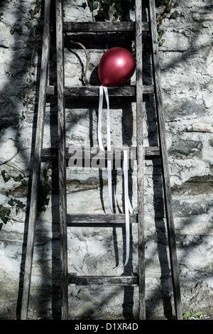 Un globo rojo sobre una antigua escalera de madera