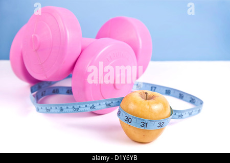 Rosa grande dumbells, manzana verde y cinta de medir, aislado en blanco.