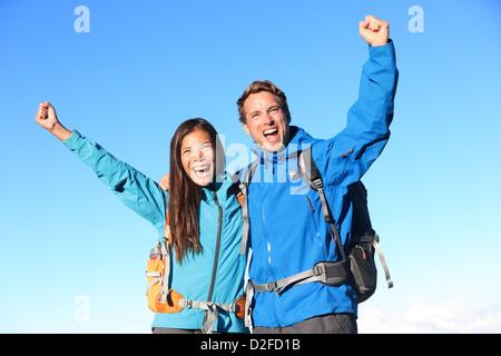Hombre y mujer joven feliz caminante vítores mientras se mantiene alrededor de otro, con los brazos levantados contra el cielo