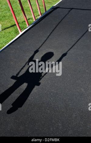 Sombra proyectada por un joven niño jugando en un columpio en un parque de juegos infantiles Foto de stock