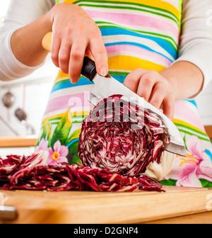 Manos de mujer Cortar el repollo rojo, detrás de las verduras frescas. Foto de stock