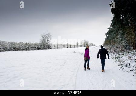 Dos personas caminando a través de la campiña de Essex cubiertos de nieve. Foto de stock