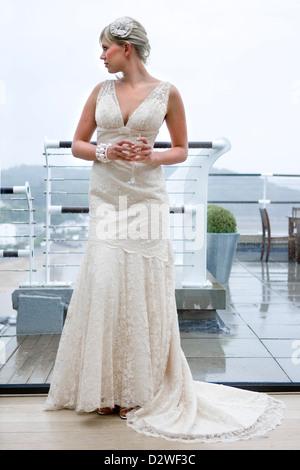 Una hermosa joven rubia novia mirando por una ventana mientras espera para su ceremonia de boda.